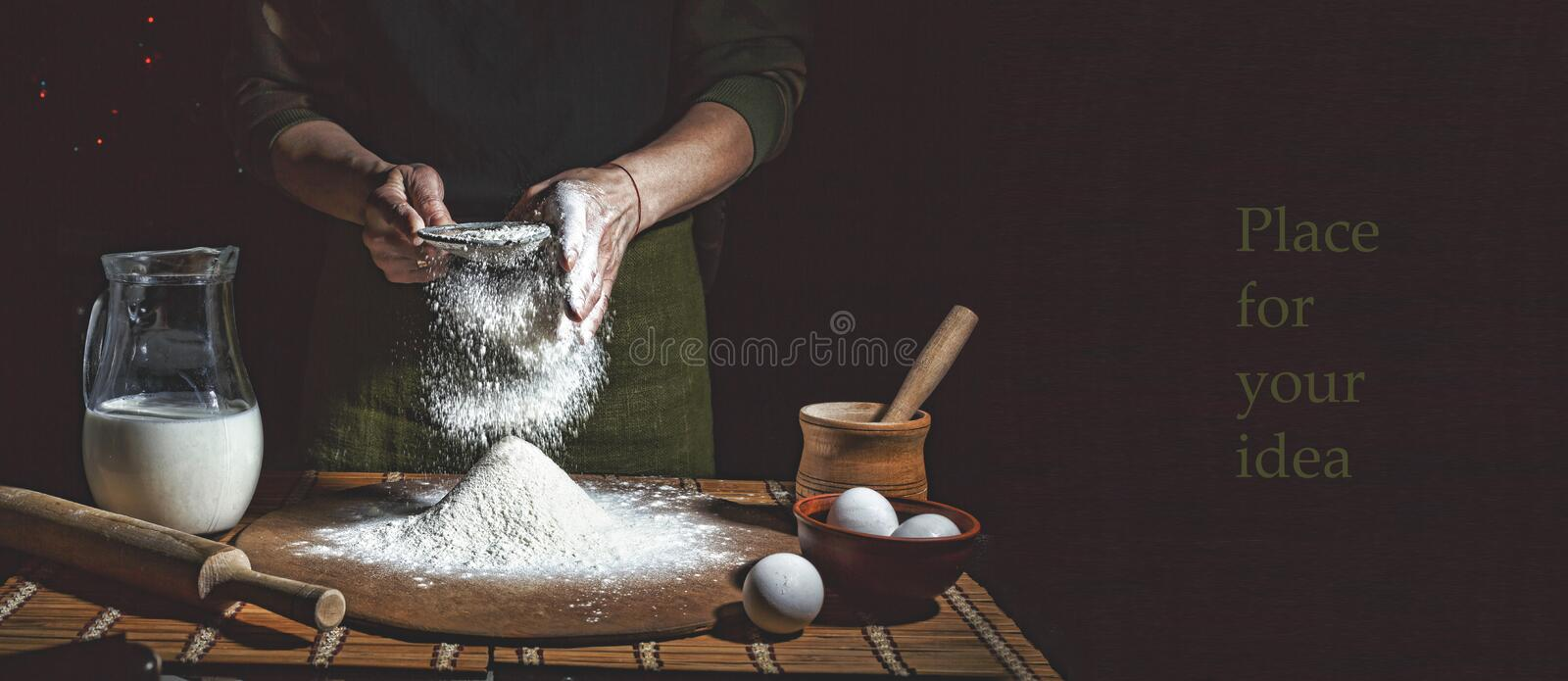 Preparation of bread dough. Bakery, baker`s hands, flour is poured, flying flour stock photography