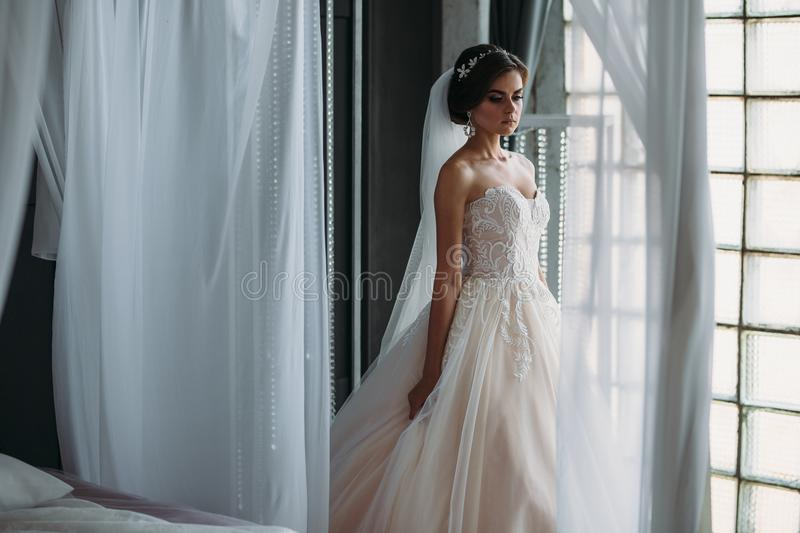 Preparation of the bride on a wedding day. Beautiful brunette girl in a white luxury dress, with earrings, make-up and. Hairdo posing in a dark studio. Concept stock photography