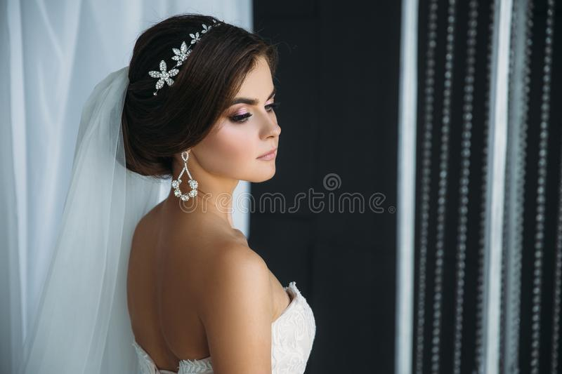 Preparation of the bride on a wedding day. Beautiful brunette girl in a white luxury dress, with earrings, make-up and. Hairdo posing in a dark studio. Concept royalty free stock photos