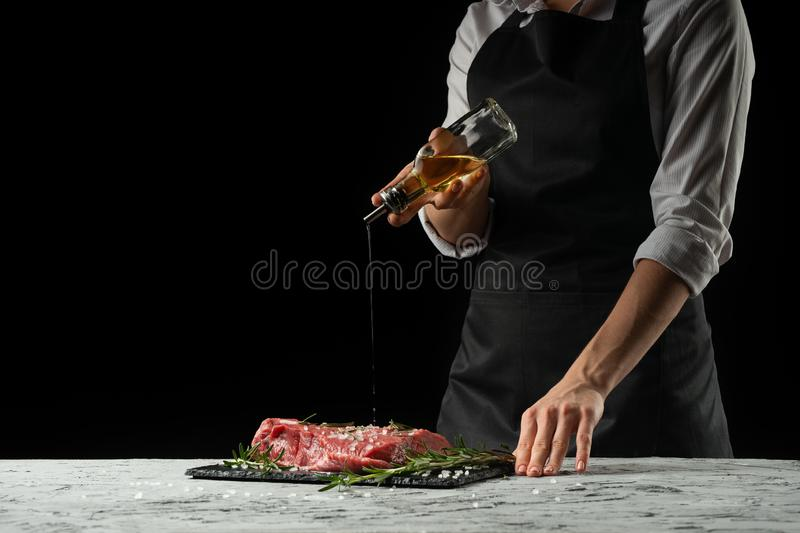 Preparation of the chef by steak cook.Preparation of fresh beef or pork. Horizontal photo with dark black background. royalty free stock image