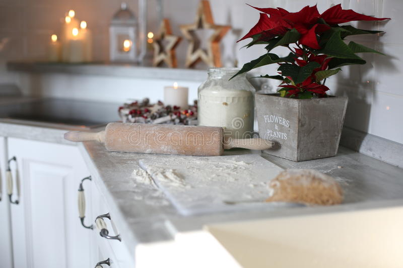 Preparation of Christmas sweets. Flour, rolling pin and a New Year`s flower on the table royalty free stock image