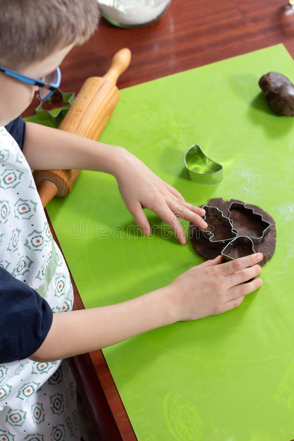 Preparation of cinnamon cookies. The boy puts the metal molds on the rolled piece of dough. royalty free stock image