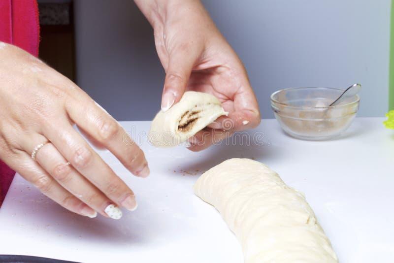 Preparation of cinnamon rolls. The woman cuts the workpiece into rolls into separate rolls. stock photography