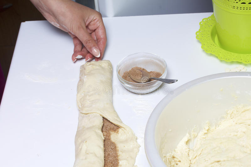 Preparation of cinnamon rolls. The woman turns off the dough with a filling of cinnamon and sugar. Preparation of cinnamon rolls. The woman turns off the dough stock image