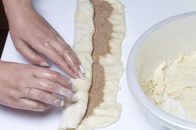 Preparation of cinnamon rolls. The woman turns off the dough with a filling of cinnamon and sugar. Preparation of cinnamon rolls. The woman turns off the dough stock photography