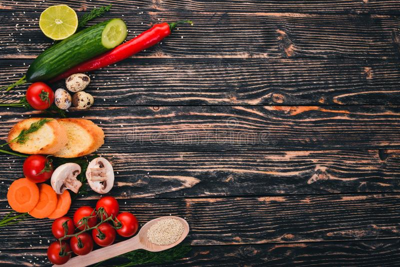 Preparation for cooking. Cherry tomatoes, baguette, quail eggs, cucumber, mushrooms. On a wooden background. Top view. Copy space royalty free stock image