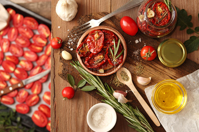 Preparation dried tomatoes. Raw and dried tomatoes arranged over on old wooden table with spice and herbs. Baking tray with raw tomato. Rustic stile. Organic royalty free stock photos