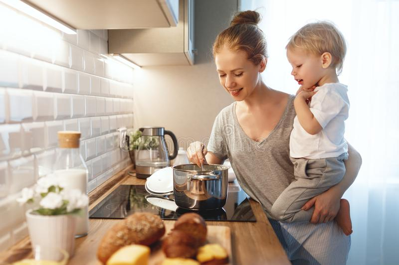 Preparation of family breakfast. mother and baby son cook porridge in morning. Preparation of a family breakfast. mother and baby son cook porridge in morning royalty free stock photos