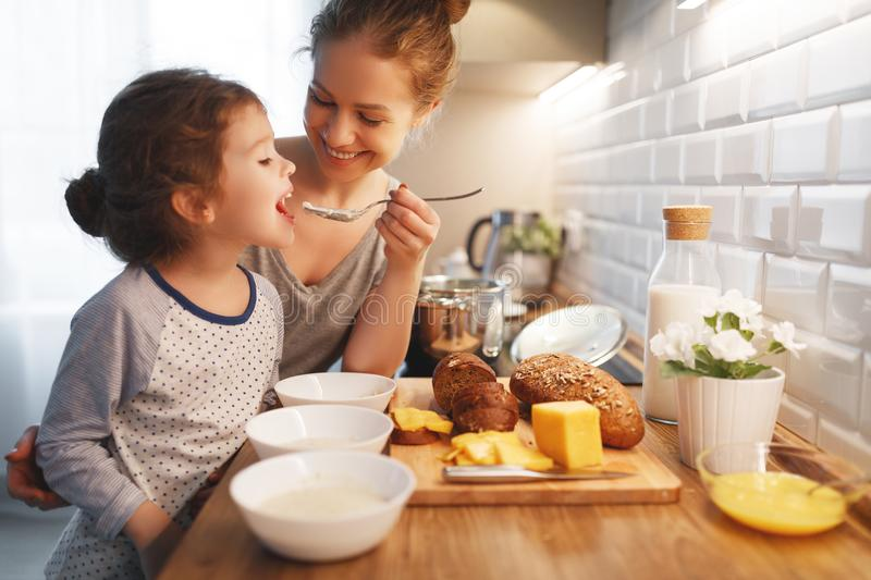 Preparation of family breakfast. mother and child daughter cook. Preparation of a family breakfast. mother and child daughter cook porridge in morning royalty free stock photography
