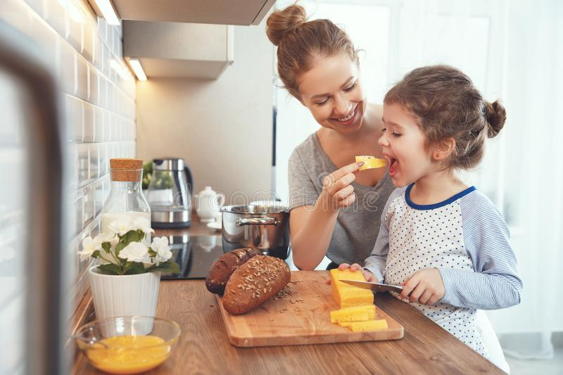 Preparation of family breakfast. mother and child daughter cut b. Preparation of a family breakfast. mother and child daughter cut bread and cheese in morning royalty free stock image