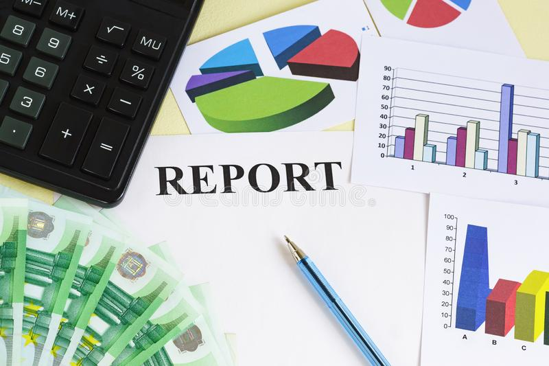 Preparation of the financial report. Money, calculator, pen, color charts and diagrams on the table stock photos