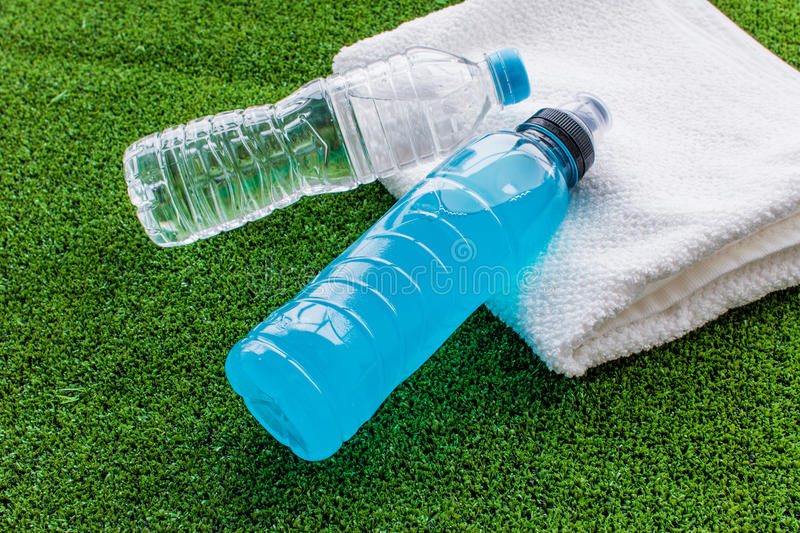 Preparation for fitness water bottle and towel on green background. Close up royalty free stock photo