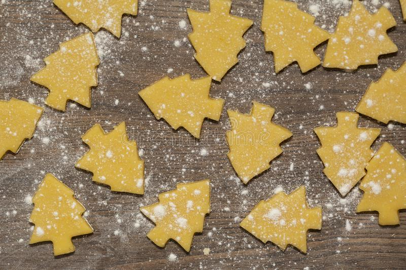 Preparation of ginger biscuits. Cutting figured cookies in form of Christmas tree. stock image