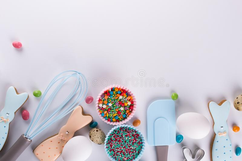 Preparation of gingerbread cookies. Easter cookies in the shape of a funny rabbit , tools necessary to make gingerbread pastry,. Colored sprinkles. Easter royalty free stock photography