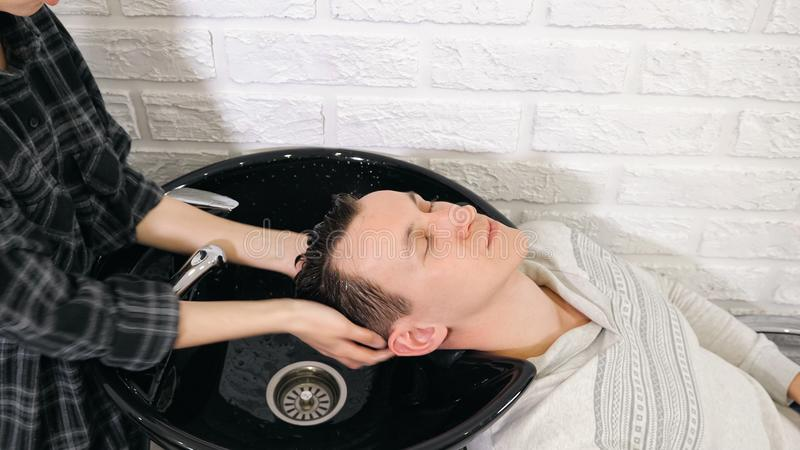 Preparation for haircut. Barber washing men`s hair on the head in barbershop stock photography