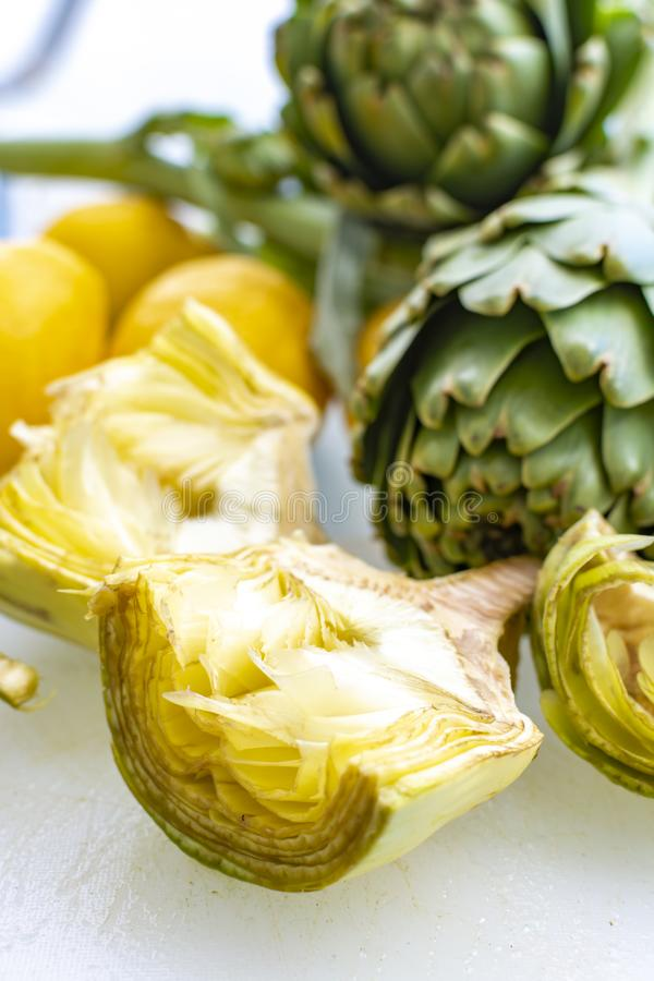 Preparation of heads of fresh raw artichokes plants from artichoke plantation in Argolida, Greece ready to cook with lemon. Preparation of heads of fresh raw royalty free stock photo