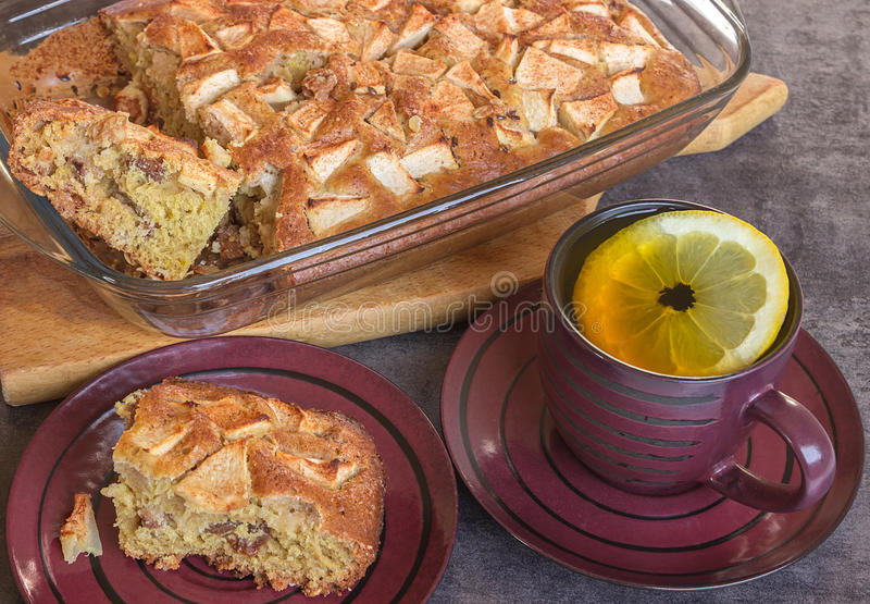 Preparation of homemade apple pie. Cup of tea with lemon. stock photos