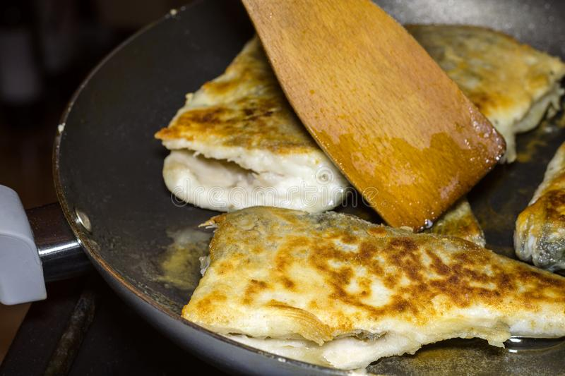 Preparation of homemade fried fish hake on a frying pan. The con stock image
