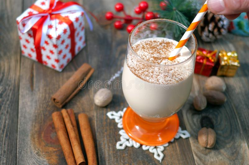 Preparation homemade traditional christmas spicy hot drink eggnog with ground nutmeg, cinnamon in a glass, for funny christmas stock images