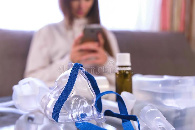Preparation for inhalation. Nebulizer, mask and medicine on the glass table. Woman with mobile phone. Preparation for inhalation. Nebulizer, mask and medicine stock photos