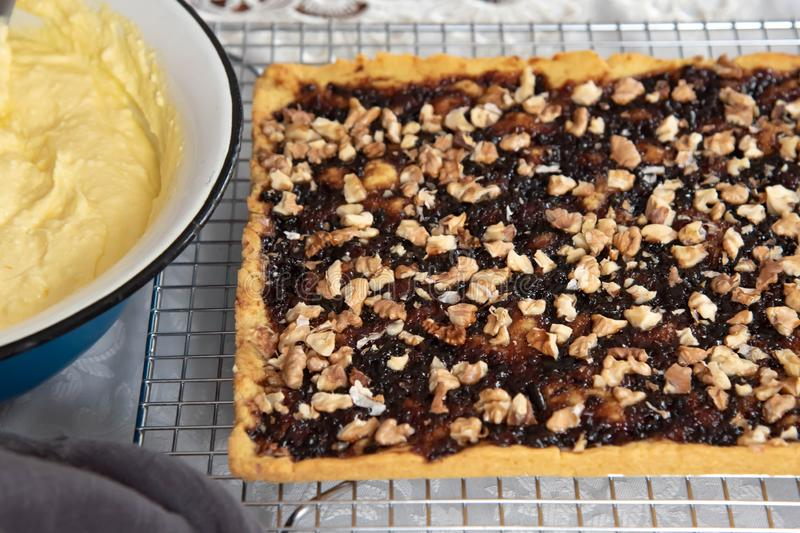 Preparation for making a cake. Shortbread pie with jam and walnuts on cooling rack. Home made custard cream for cake royalty free stock image
