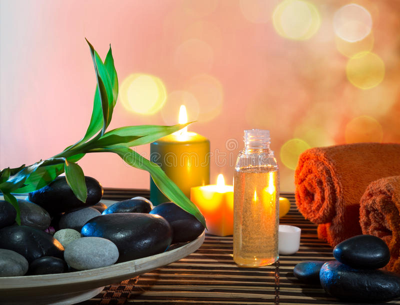 Preparation for massage in orange with dish, oil and bamboo stock images