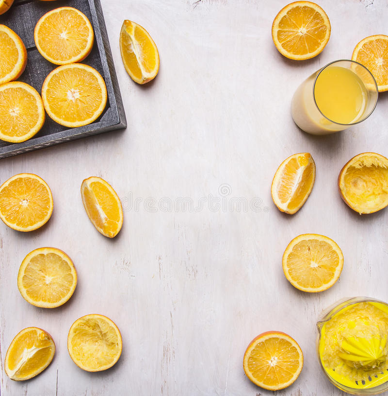 Preparation of orange juice, sliced oranges, juicer manual place for text,frame on wooden rustic background top view close up stock image