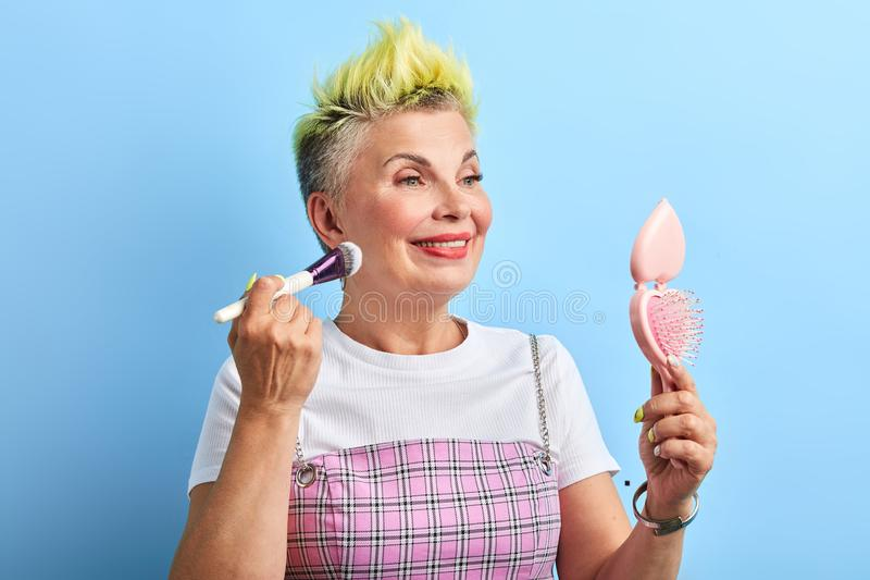 Preparation for a party.old awesome cool woman takes care of her skin. Preparation for a party.smiling granny has changed her style, hair, new life. old woman is stock photography
