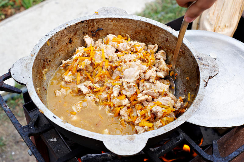 Preparation pilaf in the cauldron on fire stock photo