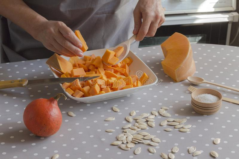 Preparation of products for making pumpkin soup. Female hands stack the chopped pumpkin in a plate. Gray Polka Dot Tablecloth royalty free stock photography