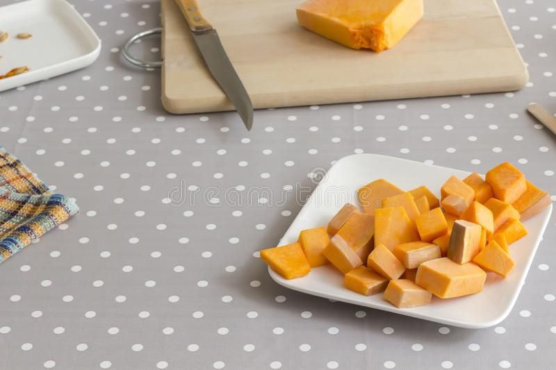 Preparation of products for making pumpkin soup. Sliced pumpkin in a white plate. Knife on a cutting board. Gray polka dot royalty free stock photography