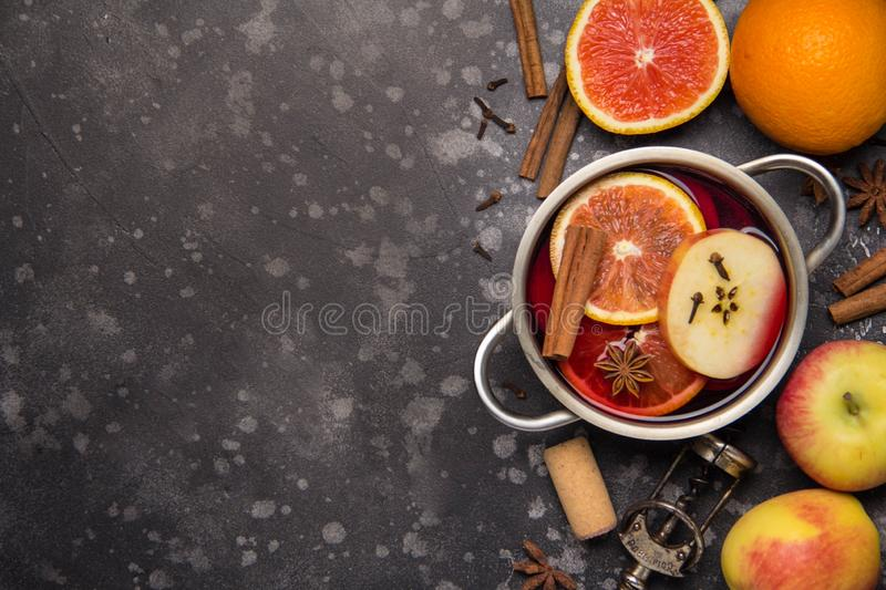 Preparation of red mulled wine with orange, apple, cinnamon, spicy autumn drink in the pan. Copy space for text, top view royalty free stock photos
