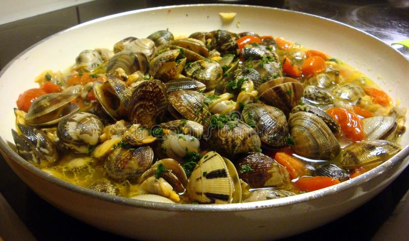 Preparation of a sauce with clams in a pan royalty free stock photos