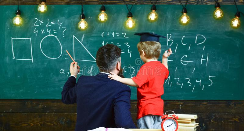 Preparation for school concept. Boy, child in graduate cap listening teacher, chalkboard on background, rear view stock images