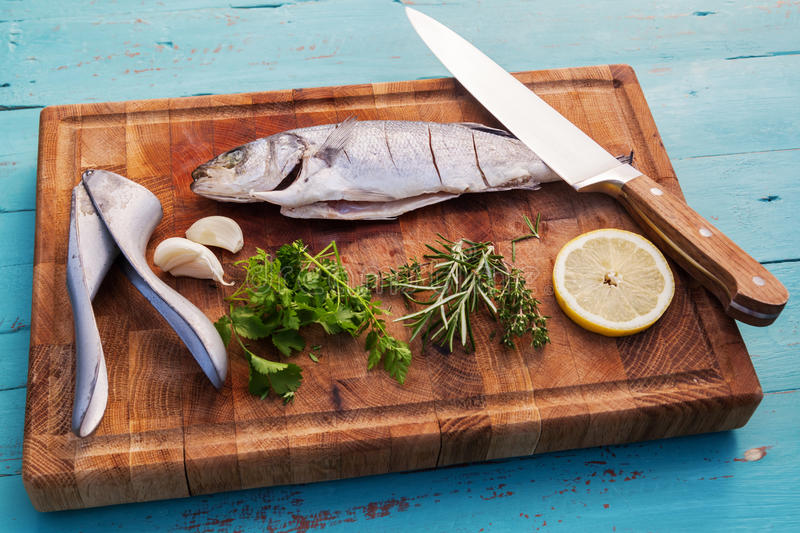 Preparation from a sea bass. With ingredients on a shopping board royalty free stock photo