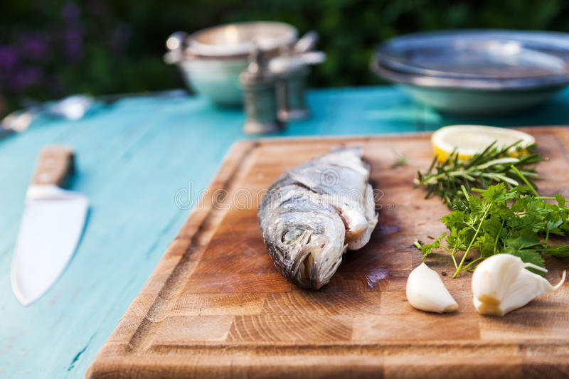 Preparation from a sea bass. With ingredients on a shopping board stock photography