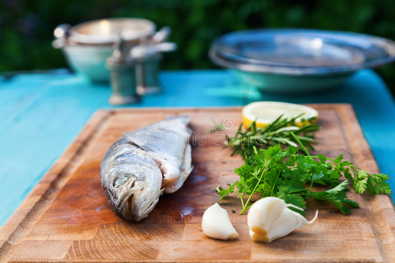 Preparation from a sea bass. With ingredients on a shopping board royalty free stock photography