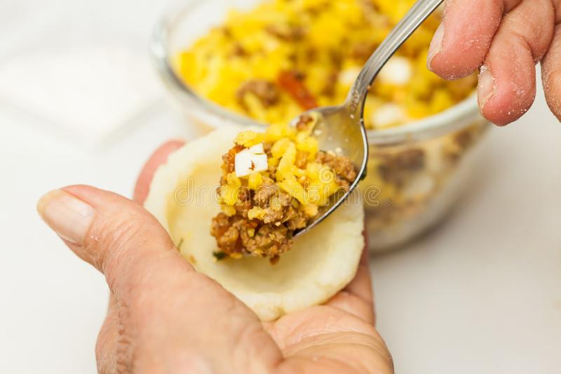 Preparation steps of traditional Colombian dish called stuffed potatoes stock image