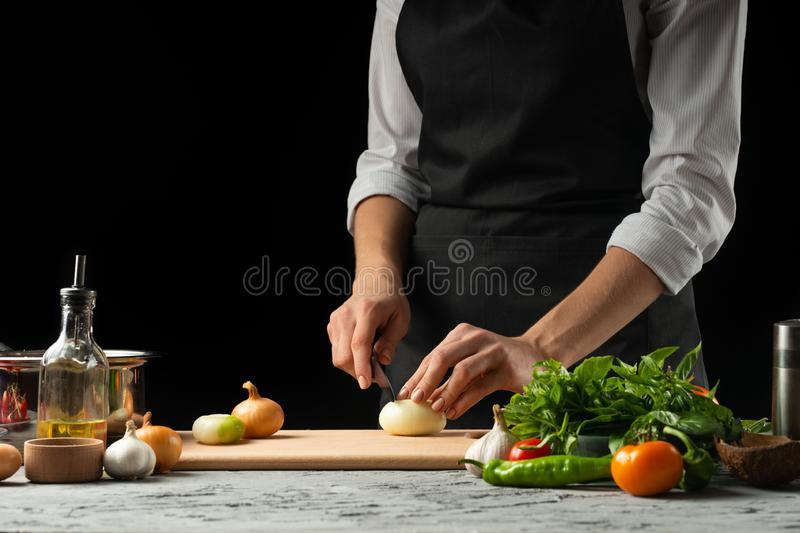 Preparation of tomato sauce by the hands of the chef, steps the process in the kitchen on a black background copy the text of the stock images
