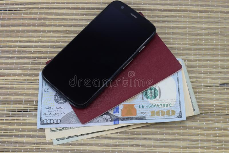 Preparation for vacation, passport with money for rest on the table and a cell phone in the way stock images