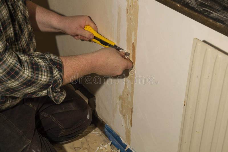 Preparation for wallpapering. A man is making the necessary ground job for wallpapering a room stock images