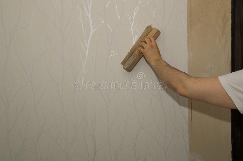 Preparation for wallpapering. A man is making the necessary ground job for wallpapering a room royalty free stock image