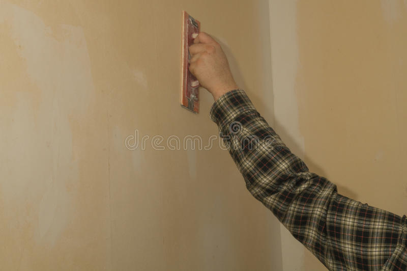 Preparation for wallpapering. A man is making the necessary ground job for wallpapering a room royalty free stock images