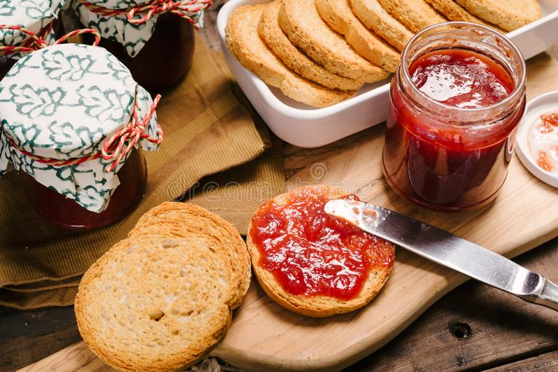 Preparations of breakfast with rusks and strawberry jam. Breakfast preparations with, toasts and strawberry jam over a wooden cutting board stock photography