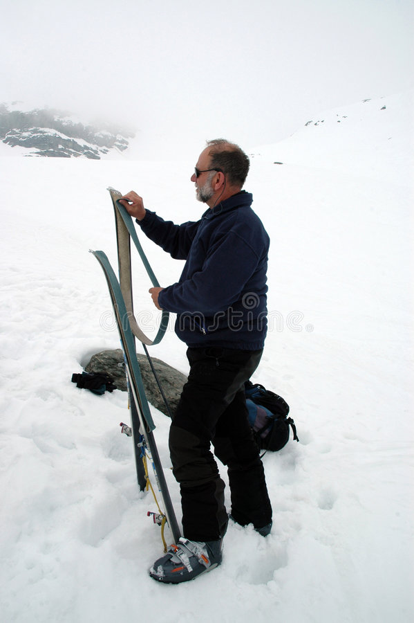 Preparations for the descent. Ski mountaineering or cross country skiing in Italian Alps. A man prepares skis for the descent stock photo