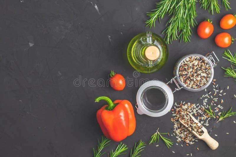 Preparato del riso in barattolo e ortaggi freschi di vetro sulla superficie strutturata concreta della pietra nera immagini stock