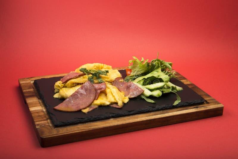 Preparato dell'omelette con le fette e l'insalata della carne fotografie stock libere da diritti