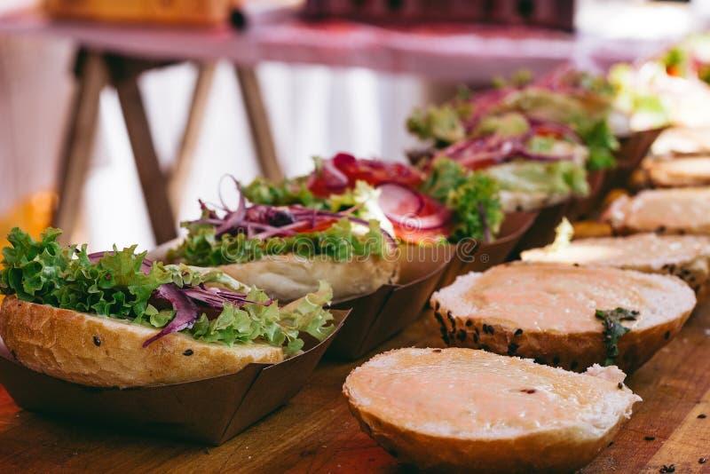 Preparazione degli hamburger deliziosi Panini freschi dell'hamburger con le verdure e la salsa sulla tavola di legno, fuoco selet fotografia stock libera da diritti