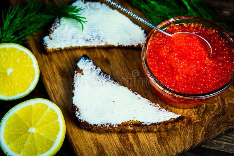 Preparazione dei panini con il caviale rosso Posto per il vostro testo immagini stock