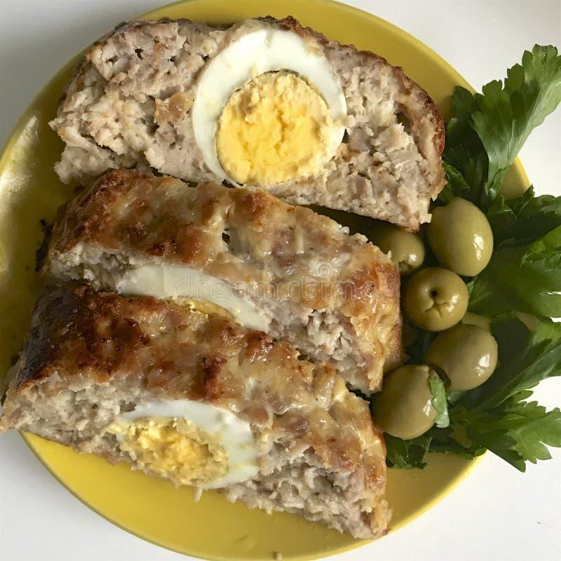 Preparazione dei polpettoni tritati Come uovo sodo di riempimento Le fette del rotolo finito sono su un piatto con le olive ed i  immagine stock